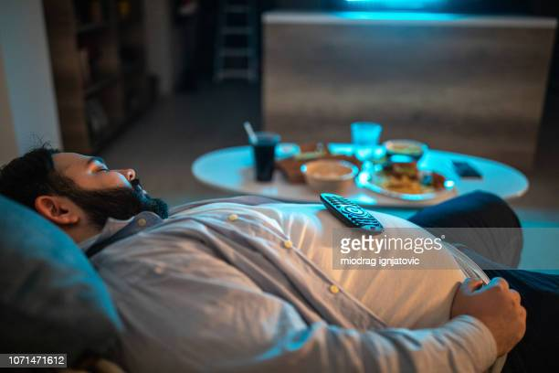 lazy man fell asleep in living room - unhealthy living stock pictures, royalty-free photos & images