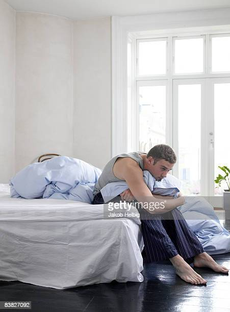 Lazy young man sitting on his bed, wearing pyjamas