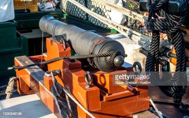 a 6 lb cannon is mounted on the deck of a 1810 wooden tall ship - 大砲 ストックフォトと画像