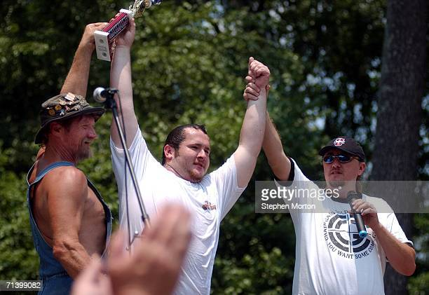 Lbow and Jeff Kidd hold up the arms of Bobbing for Pigs Feet contest winner Derek Ingram of Sandersville Georgia during the 11th annual Summer...