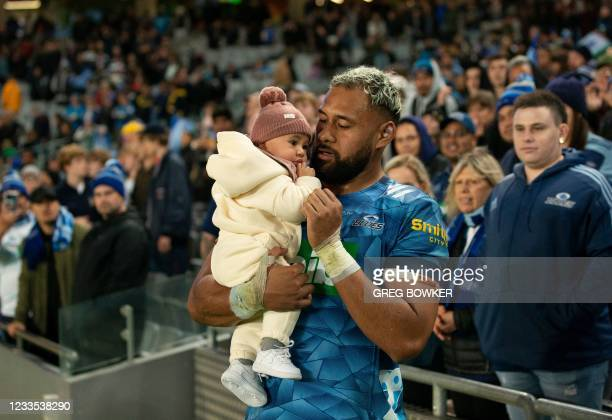 LdAuckland Blues captain Patrick Tuipulotu holds his child after the Super Rugby Trans Tasman final match against the Highlanders in Auckland on June...