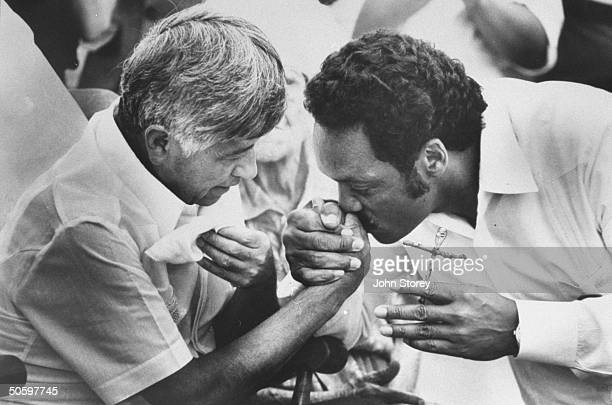 UFW ldr Cesar Chavez at mass getting his hand kissed by black ldr Rev Jesse Jackson who is passing a cross to him as he joins Chavez's fast on behalf...