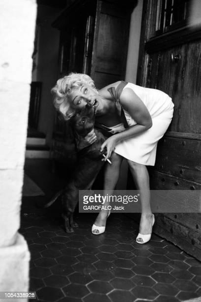 Le 11ème Festival de Cannes se déroule du 2 au 18 mai 1958 attitude souriante de Martine CAROL une cigarette à la main dans l'entrée de sa propriété...