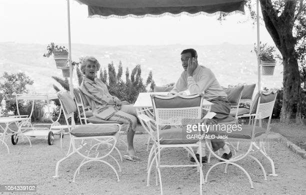 Le 11ème Festival de Cannes se déroule du 2 au 18 mai 1958 : Martine CAROL et son mari CHRISTIAN-JAQUE fumant une cigarette assis sous une tonnelle...