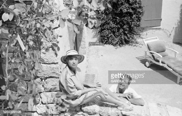 Le 11ème Festival de Cannes se déroule du 2 au 18 mai 1958 Martine CAROL coiffée d'un chapeau de paille assise sur un muret sous le regard de son...