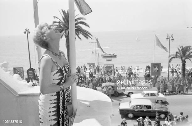 Le 12ème Festival de Cannes se déroule du 30 avril au 15 mai 1959 attitude de Martine CAROL de profil se tenant au mât d'un drapeau sur le balcon de...