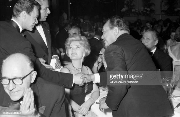 Le 12ème Festival de Cannes se déroule du 30 avril au 15 mai 1959 Edward G ROBINSON de profil tenant un cigare serrant la main d'un homme non...