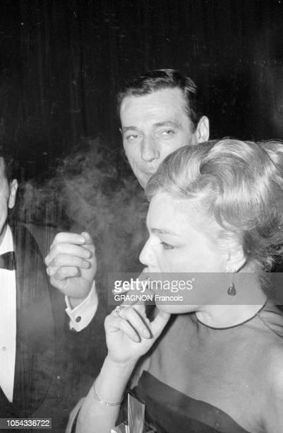 Le 12ème Festival de CANNES se déroule du 30 avril au 15 mai 1959 plan de troisquarts de Simone SIGNORET fumant une cigarette aux côtés de son mari...
