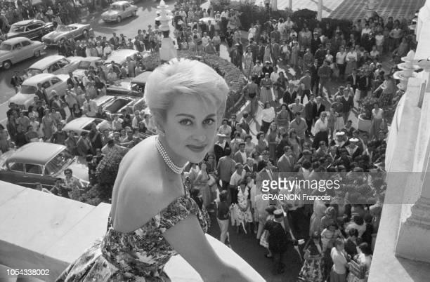 Le 12ème Festival de CANNES se déroule du 30 avril au 15 mai 1959 une foule d'admirateurs regardant Martine CAROL souriante au balcon de sa chambre...