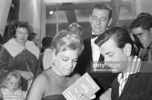 Le 12ème Festival de CANNES se déroule du 30 avril au 15 mai 1959 Yves MONTAND regardant son épouse Simone SIGNORET signer des autographes le soir de...