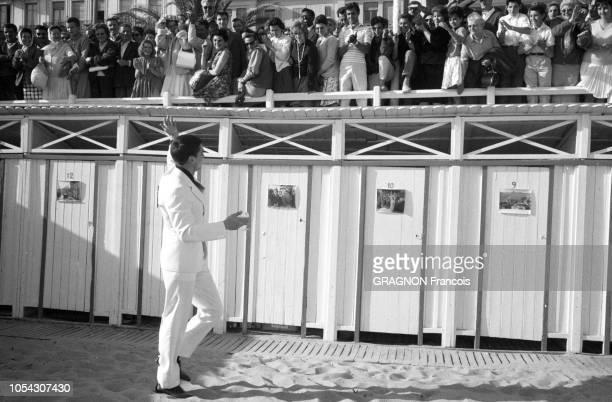 Le 14ème Festival de Cannes se déroule du 3 au 18 mai 1961 attitude souriante d'Alain DELON en costume blanc et chemise noire un verre à la main...