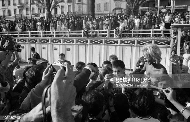 Le 14ème Festival de Cannes se déroule du 3 au 18 mai 1961 bain de foule pour Alain DELON souriant en costume blanc et chemise noire signant des...
