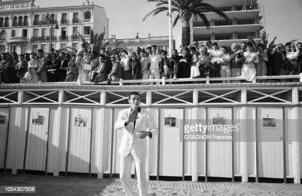 Le 14ème Festival de Cannes se déroule du 3 au 18 mai 1961 plan de face souriant d'Alain DELON en costume blanc et chemise noire un verre à la main...
