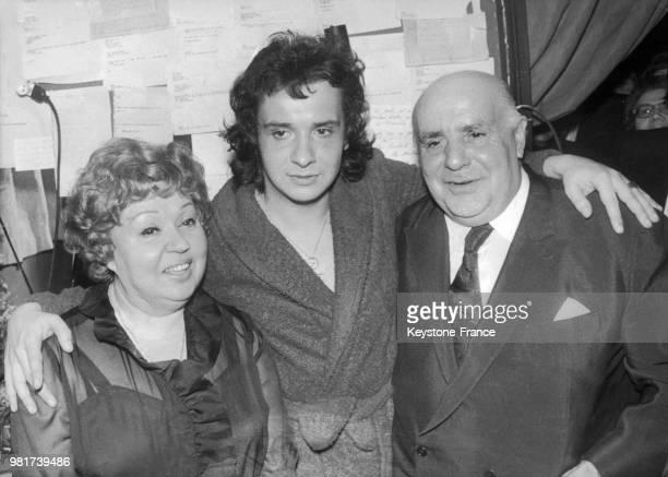 Le 18 janvier 1973, à l'Olympia de Paris en France, le chanteur français Michel Sardou pose entouré de ses parents, les comédiens Jackie et Fernand...