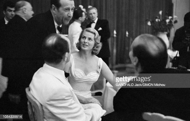 Le 9ème Festival de CANNES 1956 s'est déroulé du 23 avril au 10 mai : Georges SIMENON discutant debout à une table où sont assis Ingrid BERGMAN, son...