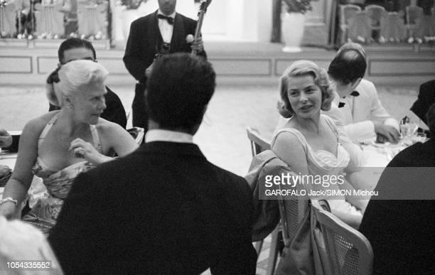 Le 9ème Festival de CANNES 1956 s'est déroulé du 23 avril au 10 mai : Ingrid BERGMAN assise à une table, se retournant pour discuter avec Jacques...