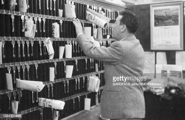 Le 9ème Festival de CANNES 1956 s'est déroulé du 23 avril au 10 mai plan de profil de FERNANDEL jouant au réceptionniste derrière le comptoir de la...