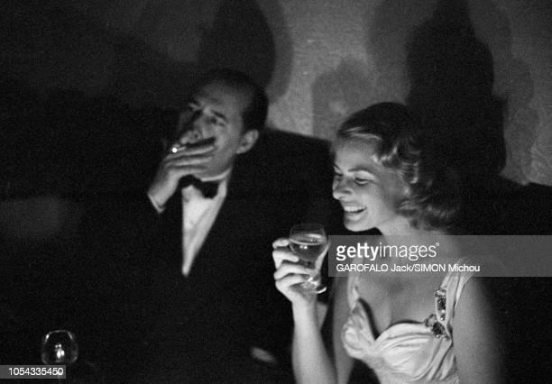Le 9ème Festival de CANNES 1956 s'est déroulé du 23 avril au 10 mai : plan de trois-quarts souriant d'Ingrid BERGMAN un verre à la main, assise aux...