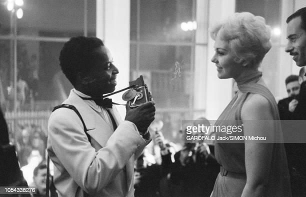 Le 9ème Festival de CANNES 1956 s'est déroulé du 23 avril au 10 mai plan de profil souriant de Kim NOVAK face à un photographe en haut de l'escalier...