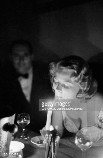 Le 9ème Festival de CANNES 1956 s'est déroulé du 23 avril au 10 mai : Ingrid BERGMAN allumant sa cigarette à la flamme d'une bougie, assise aux côtés...