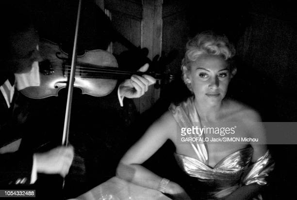 Le 9ème Festival de CANNES 1956 s'est déroulé du 23 avril au 10 mai un musicien jouant du violon pour Martine CAROL assise à une table lors d'une...