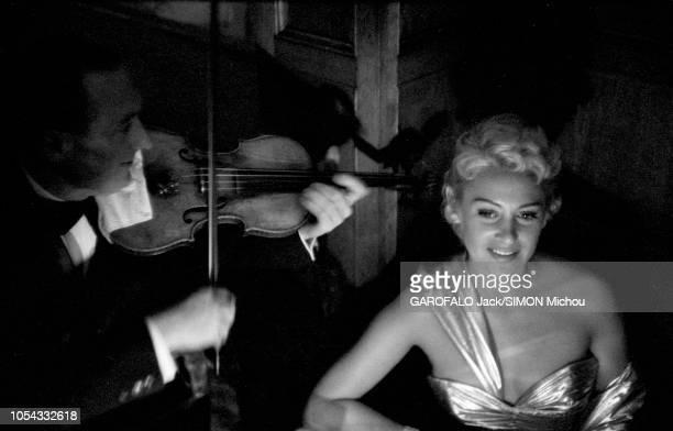 Le 9ème Festival de CANNES 1956 s'est déroulé du 23 avril au 10 mai un musicien jouant du violon pour Martine CAROL souriante assise à une table lors...