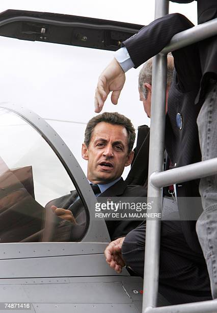 French President Nicolas Sarkozy speaks with Dassault Aviation chairman Charles Edelstenne as he sits in the cockpit of a French Dassaultmade Rafale...