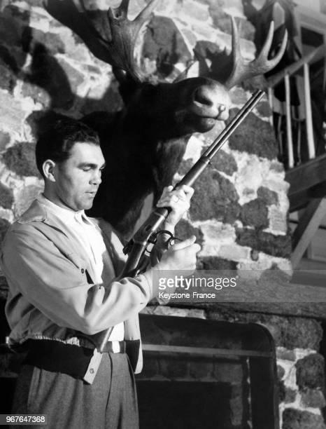 Le boxeur allemand Max Schmeling charge un fusil près d'une cheminée avec un trophée de chasse au quartier général de son entraînement le 27 mai 1938...