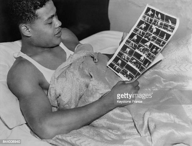 Le boxeur américain et champion du monde Joe Louis regarde les photographies représentant les phases de son dernier match allongé dans son lit aux...