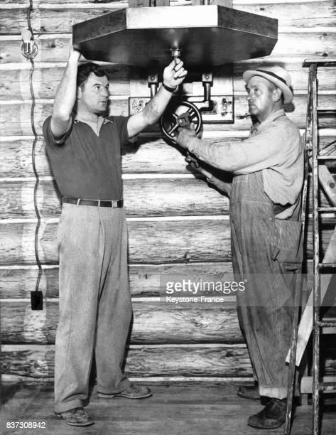 Le boxeur américain Jimmy Braddock aide un ouvrier à ajuster la plateforme de fixation d'un punchingbag au gymnase Karl Ogren le 8 avril 1937 à Stone...
