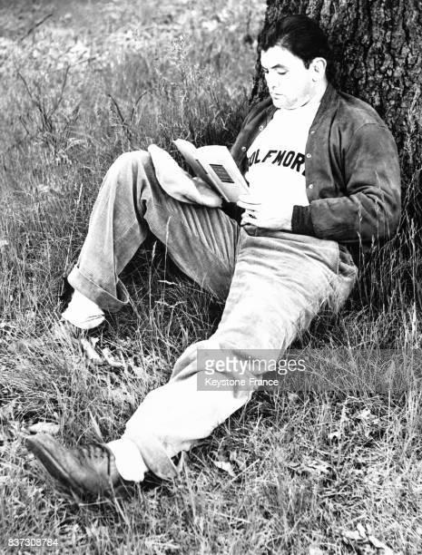 Le boxeur américain Jimmy Braddock lit 'Des Souris et des hommes' de Steinbeck au pied d'un arbre lors d'une pause détente au cours de son...