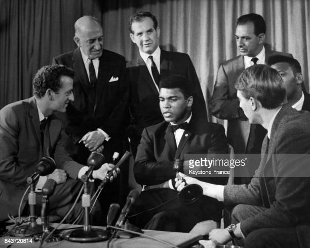 Le boxeur américain Mohamed Ali Harry Levene l'organisateur Mickey Duff et l'entraîneur Angelo Dundee lors d'une conférence de presse à l'aéroport de...