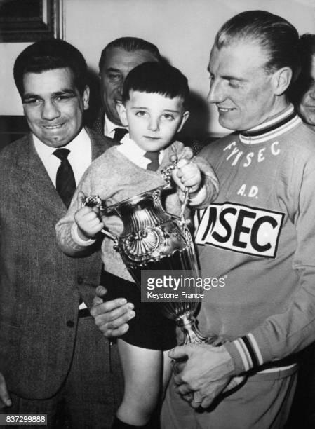 Le boxeur Duilio Loi et André Darrigade tenant dans ses bras le fils de Fausto Coppi Faustino Coppi lors du tour de Sardaigne en Italie le 29 février...