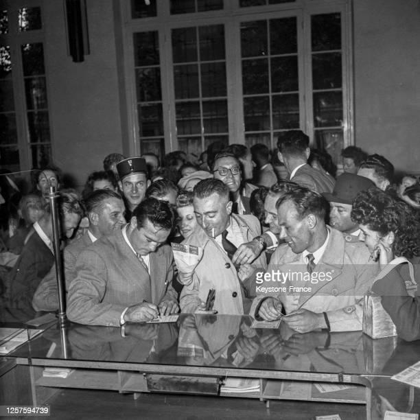 Le boxeur français Marcel Cerdan signant des autographes avant son départ pour les Etats-Unis, dans la gare des Invalides, le 23 août 1948, à Paris,...