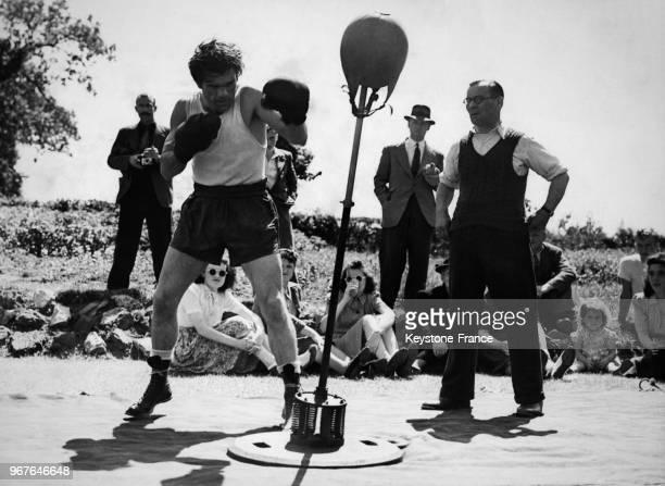 Le boxeur Freddie Mills s'entraîne sur un punchingball en plein air le 20 juillet 1948 à Dorking RoyaumeUni