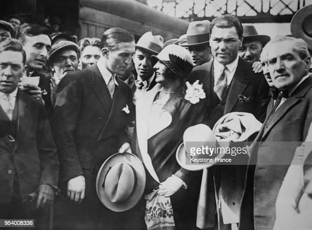 Le boxeur Georges Carpentier photographié avec le joueur de football américain Franck Dempsey et son épouse à leur arrivée à Paris, France.