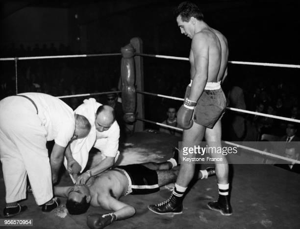 Le boxeur Gustav Scholz regarde avec incrédulité son adversaire Tuzo Portuguez à terre après 60 secondes de match le 5 décembre 1958 à Munich...