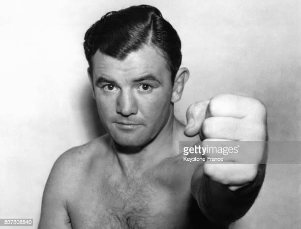 Le boxeur Jimmy Braddock brandit son poing pour indiquer qu'il est de nouveau apte au combat après une blessure à la main le 23 novembre 1936 à New...