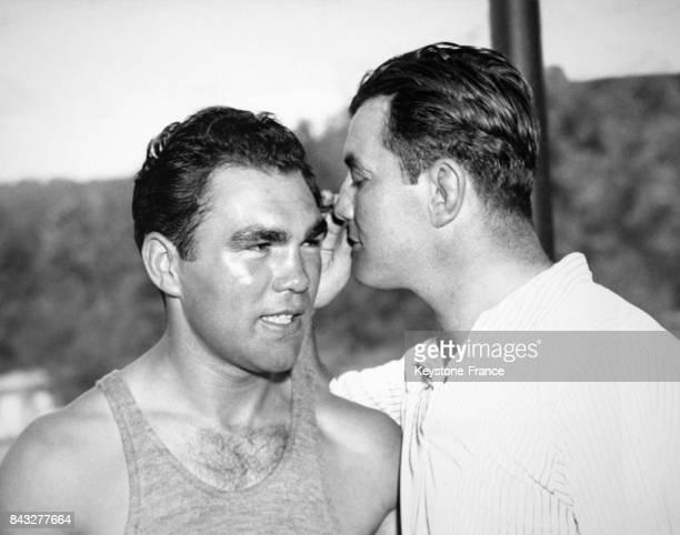 Le boxeur Jimmy Braddock chuchote à l'oreille de l'Allemand Max Schmeling lors de l'entraînement de ce dernier en prévision de son match contre Joe...
