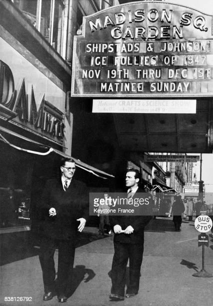 Le boxeur Marcel Cerdan se promenant dans les rues de New York passe devant une affiche de Madison Square Garden à New York City EtatsUnis en...
