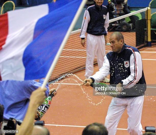 le capitaine de l'équipe de France de tennis Guy Forget arrose ses équipiers avec de la bière le 22 septembre 2001 au palais des sports Ahoy de...