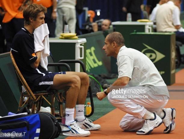 le capitaine de l'équipe de France de tennis Guy Forget donne des conseils au joueur français Nicolas Escudé le 21 septembre 2001 à Rotterdam au...
