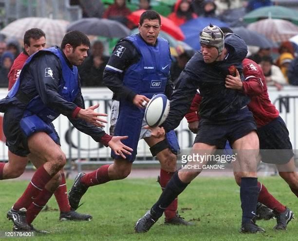 le capitaine de l'équipe de France Fabien Pelous passe le ballon au 2ème ligne David Auradou sous les yeux d'Abdelatif Benazzi le 28 mars 2001 au...