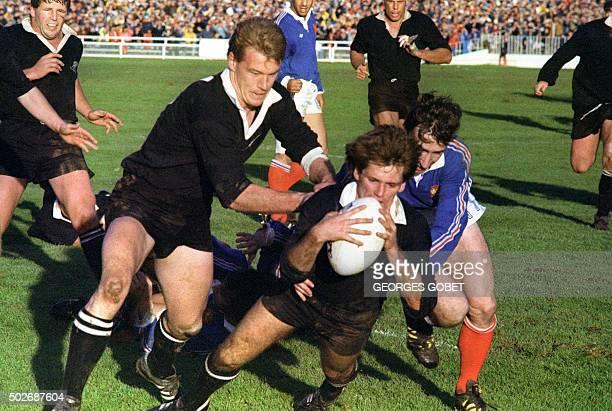 le capitaine et demi de mêlée de l'équipe de NouvelleZélande de rugby David Kirk soutenu par son coéquipier John Kirwan marque un essai malgré le...