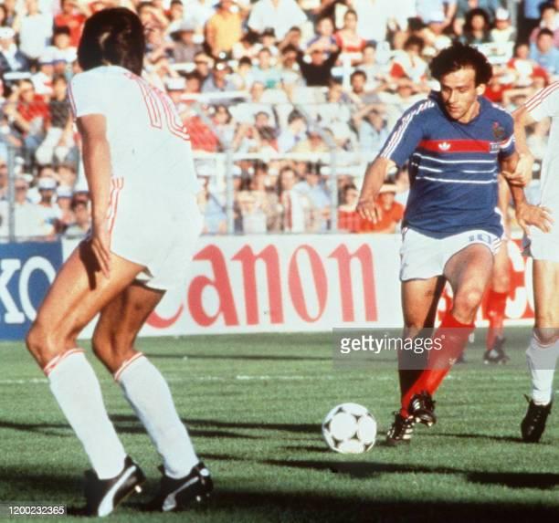Le capitaine et milieu de terrain français Michel Platini effectue une passe sous le regard de son vis-à-vis portugais, le 23 juin 1984 au stade...