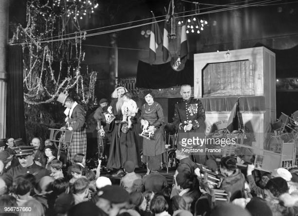 Le capitaine Villmain et le Père Noel distribuant des jouets lors du Noël des enfants à Paris France en décembre 1934