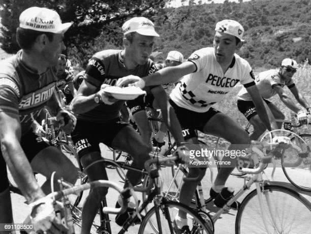 Le champion belge Merckx essaie de prendre avec ses mains une poignée de pâtes durant la 8e étape au centre le favori italien Motta à Cosenza Italie...