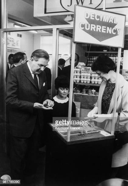 Le chancelier de l'Échiquier James Callaghan et son épouse Audrey payant avec de la monnaie décimale spécialement frappée pour la circonstance et pas...