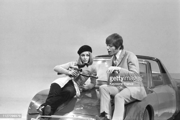 Le chanteur américain Georgie Fame avec une femme assis sur le capot d'une voiture dans le style 'Bonnie and Clyde' lors de l'enregistrement de...