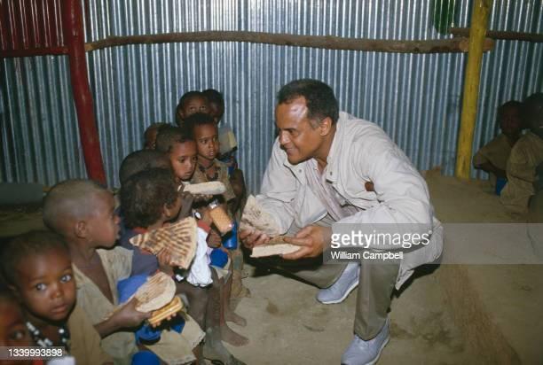 Le chanteur américain Harry Belafonte participe a la distribution de nourriture aux réfugiés en Ethiopie, provenant des gains de la vente du disque «...